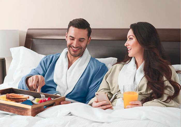 Dad and mom relax in bed in Sobel at home luxury hotel robes