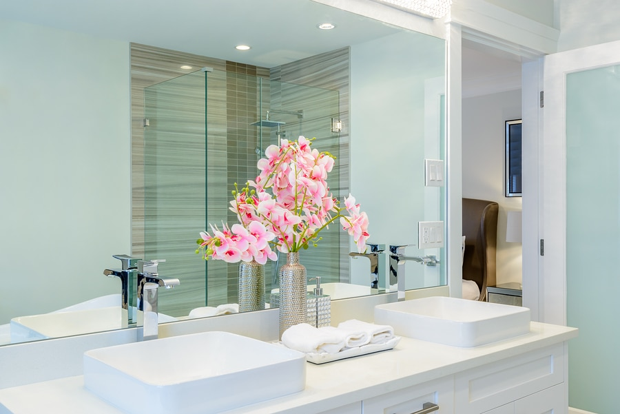 luxury hotel bathroom with orchids and white folded hand towels next to the sink