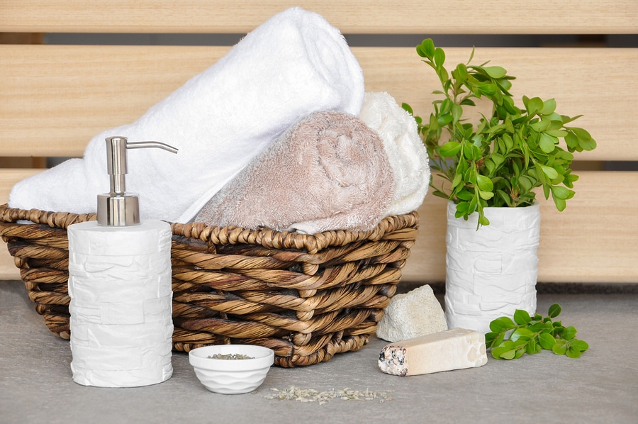 soapherbs sponge and towels in a wicker basket on a light background