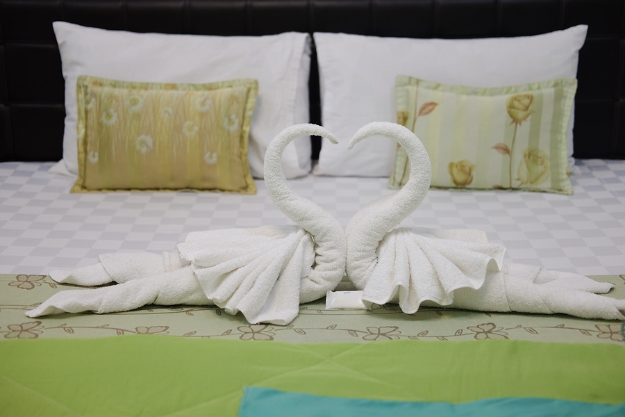Pillow and blown pillow and fold the towel as a swan kiss each other on the white bed