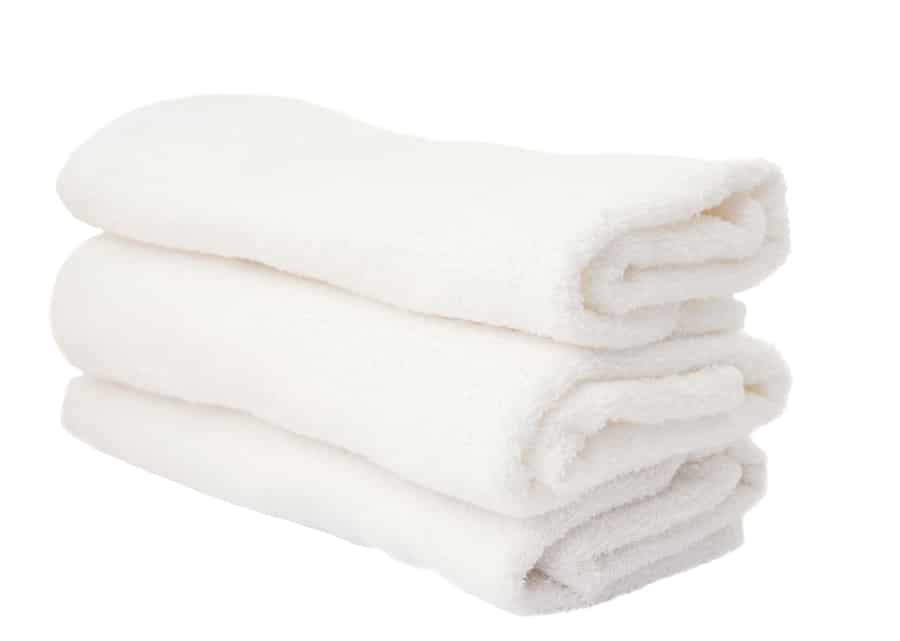 fluffy white hotel towels folded and stacked
