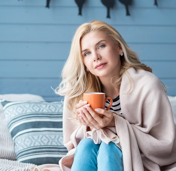 Beautiful blond woman sitting in bedroom covered with warm blanket