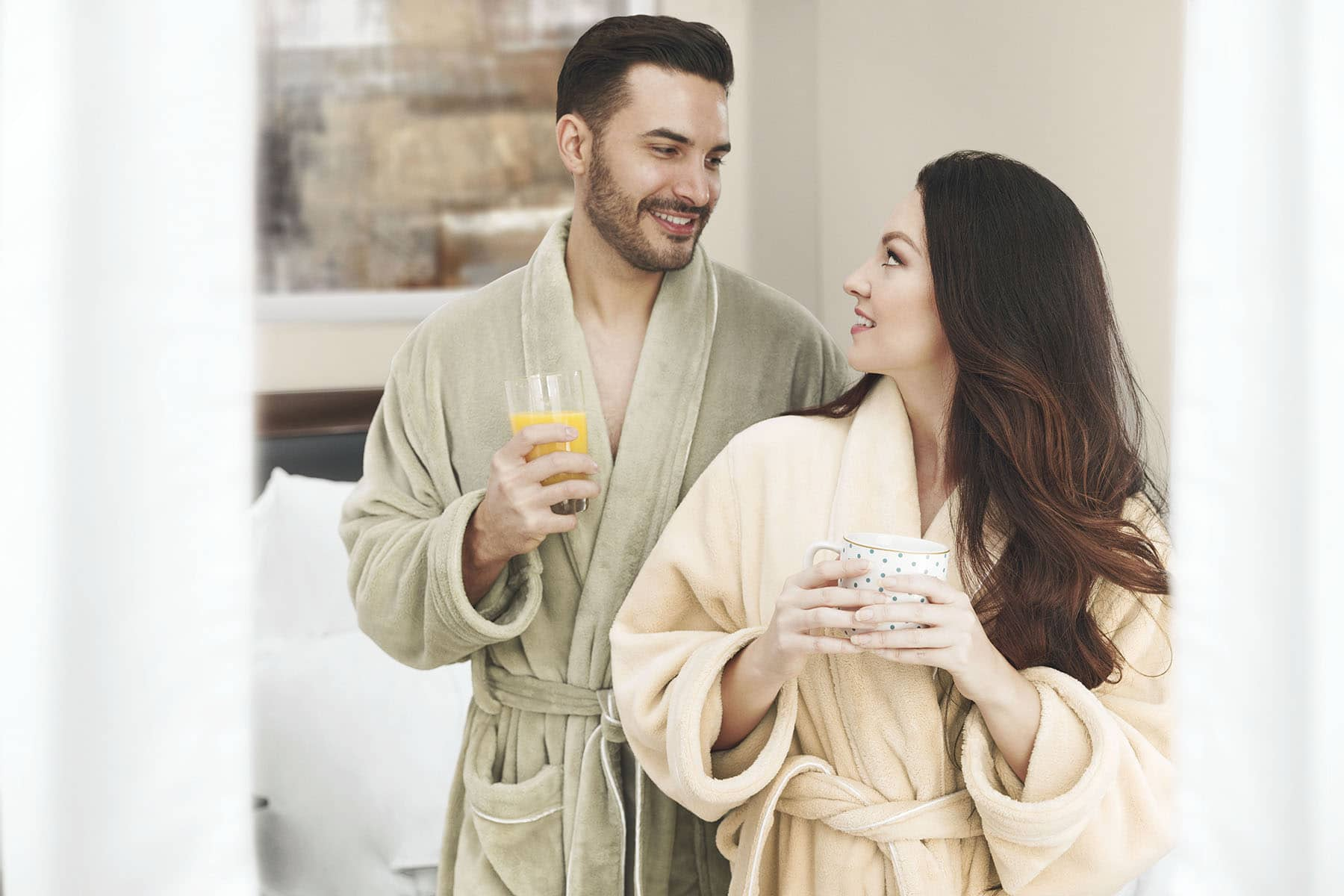 Models in urbana robes at home enjoying coffee and juice