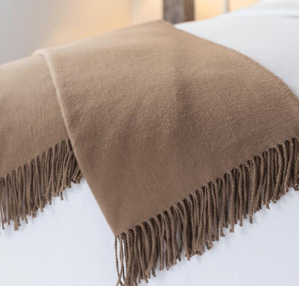 Sobel Westex alpaca blanket in brown on a white hotel bedspread