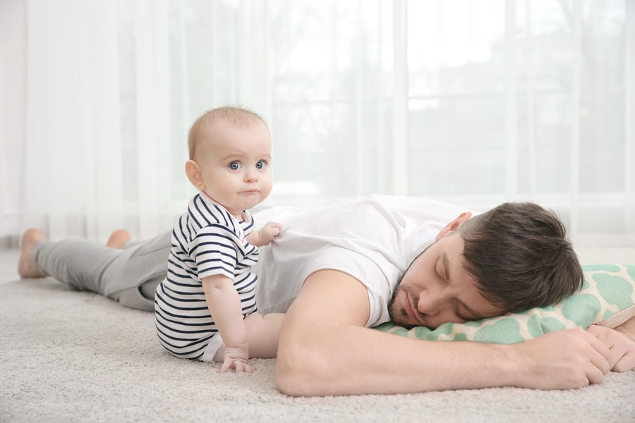 Tired dad asleep on old pillow on carpet while baby looks confused