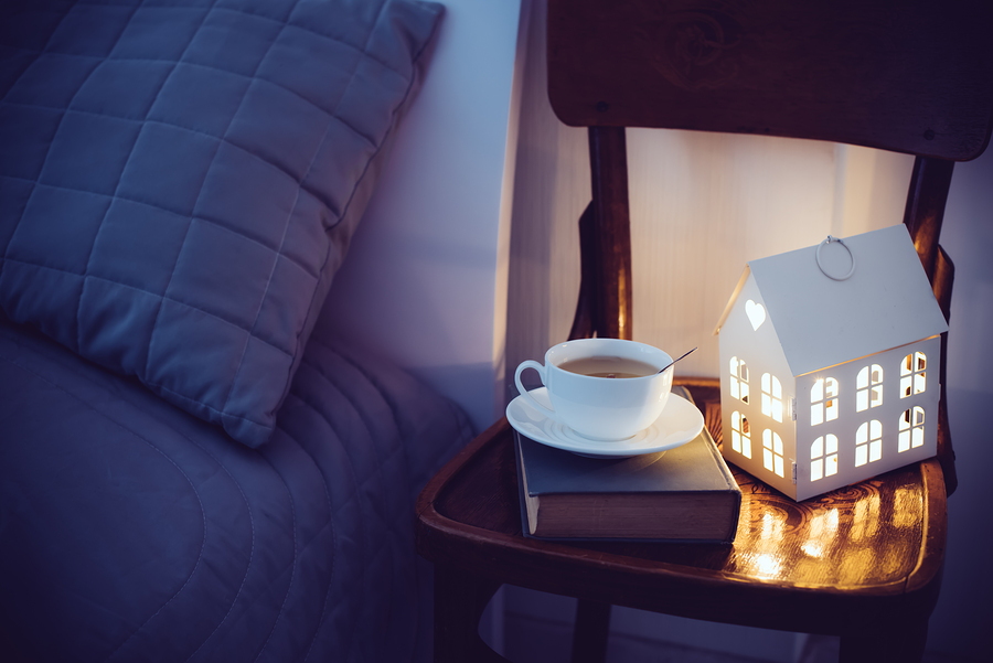 Cozy evening bedroom interior, cup of tea and a night light on the bedside table. Home