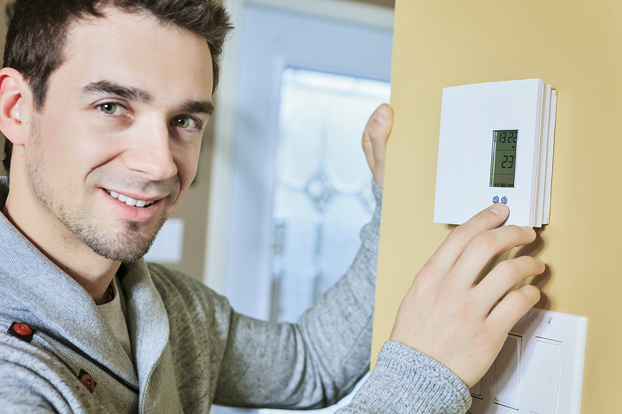 A man set the thermostat in winter at house.