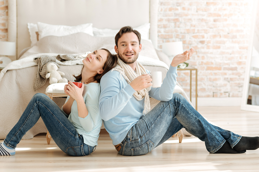 Enjoying positive mood. Happy smiling charming couple sitting in the bedroom back to back while expressing care and drinking hot tea with lemon