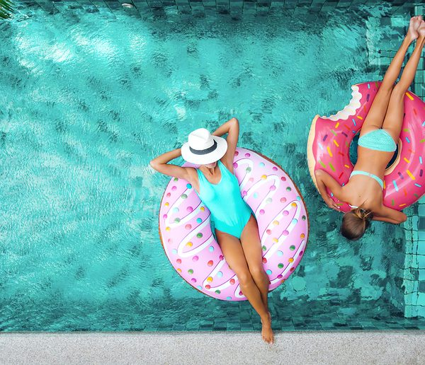 Swimming pool from overhead with mom and daughter lounging on doughnut shaped floats.