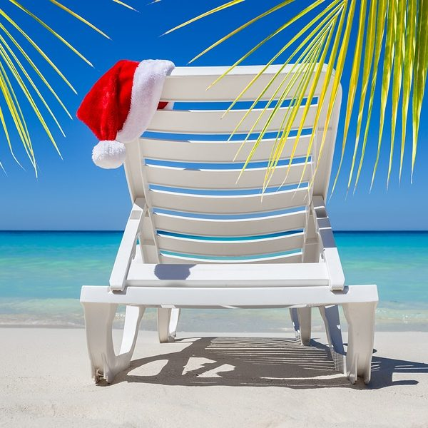 Christmas in July with santa hat on a chaise lounge on a tropical beach