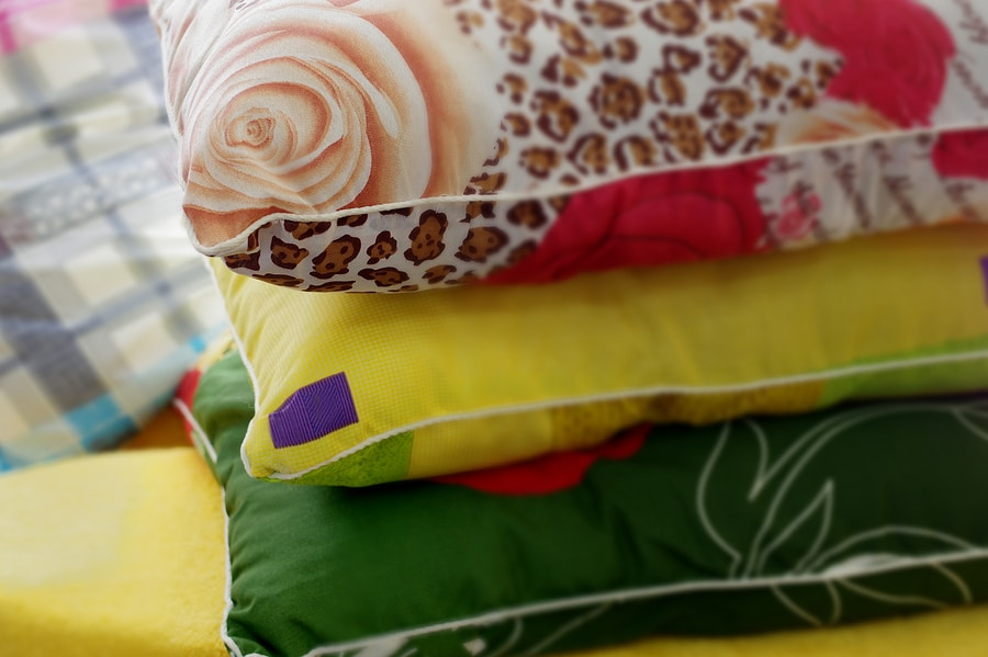 Three colorful pillows and pillowcases stacked in a pile