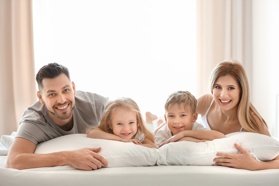 Happy family on bed with pillows denoting healthy lifestyle pillow fillings