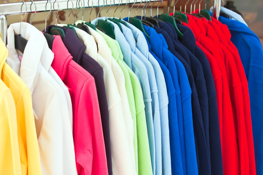 colorful fleece jackets hanging in row at store