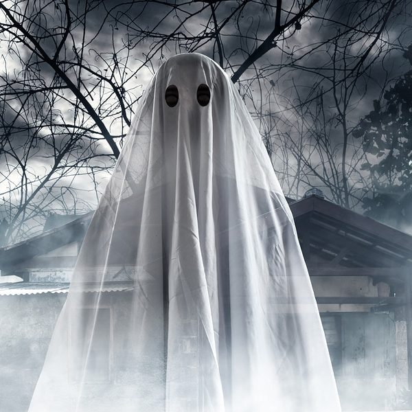Halloween ghost in bed sheet costume in front of foggy haunted house and trees
