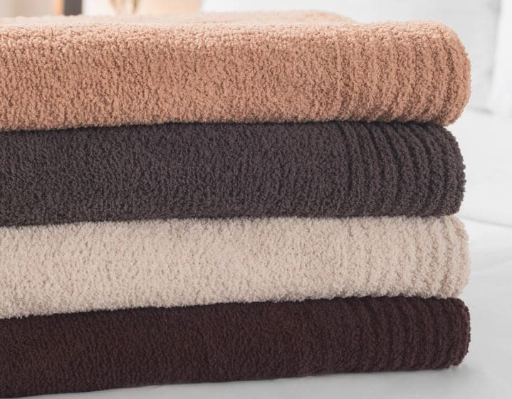 Four Sobel Westex chenille blankets stacked in different colors