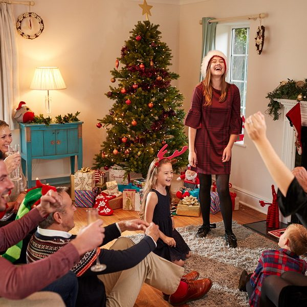 Multi Generation Family Playing Charades As They Celebrate Christmas At Home Together