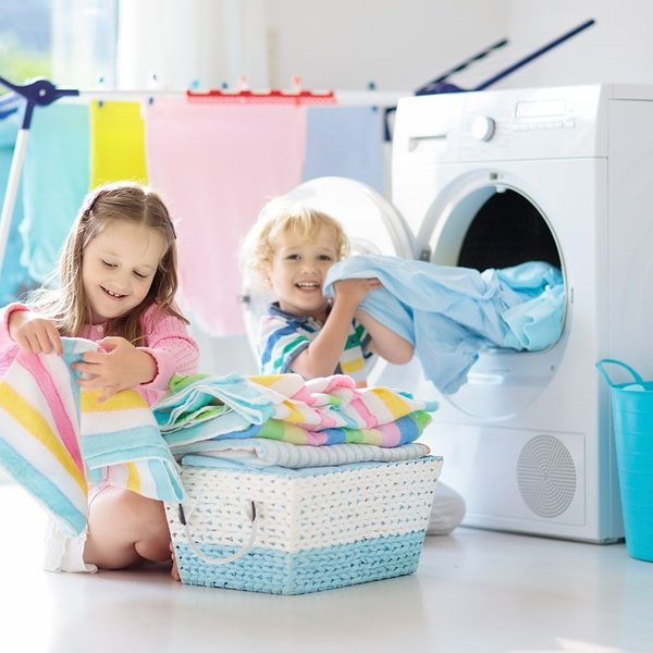 Children in laundry room sorting clean towels in front of dryer.