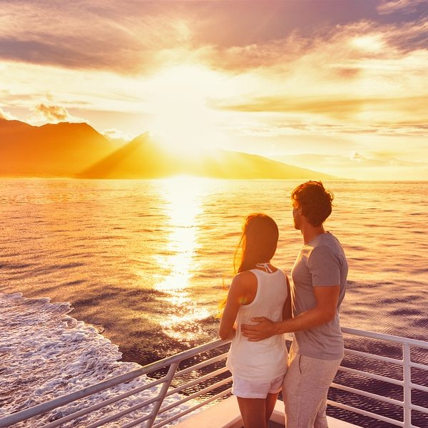 Couple watch sunset from deck of a luxury cruise ship