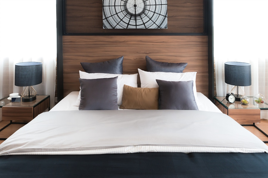 hotel bed with neat crisp percale sheets and brown and gold matching pillows