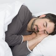 man with beard sleeping on his side on a comfortable pillow for a side sleeper