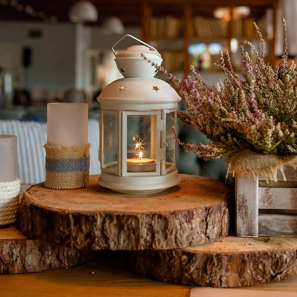 fall season home decoration made of cozy candles and dried floral arrangement on wood blocks with home in background