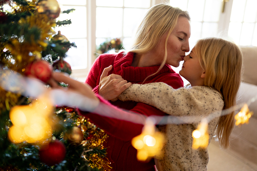Young mom kissing her young daughter while exchanging holiday gifts under a beautifully let Christmas tree