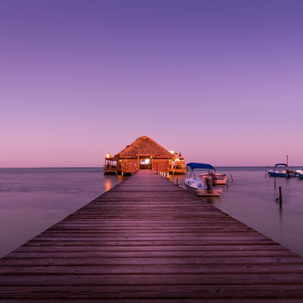 dream vacation bungalo lit up at sunset over water near great blue hole, belize
