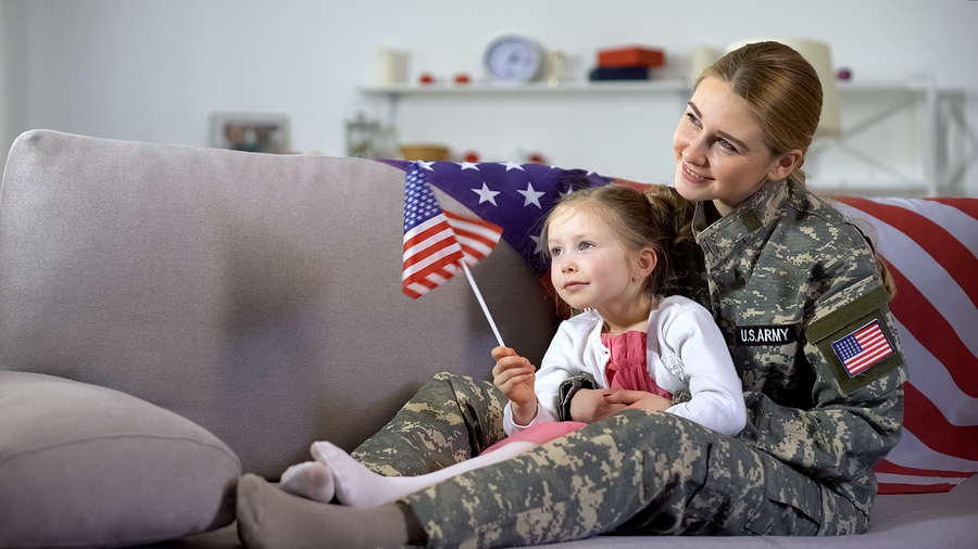 American female service member and little daughter at home on the sofa with flag watching armed services celebration