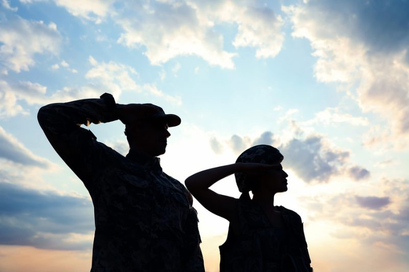 Soldiers in uniform saluting against the sky at armed forces celebration