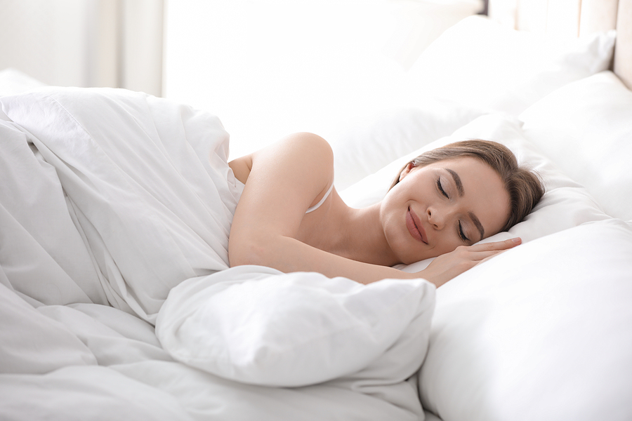 Young woman sleeping on comfortable luxury pillow in bed at home