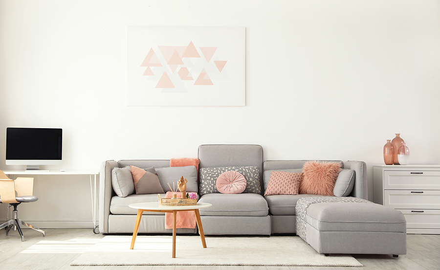 Modern living room interior with comfortable sofa and throw pillows of different shapes, textures and colors