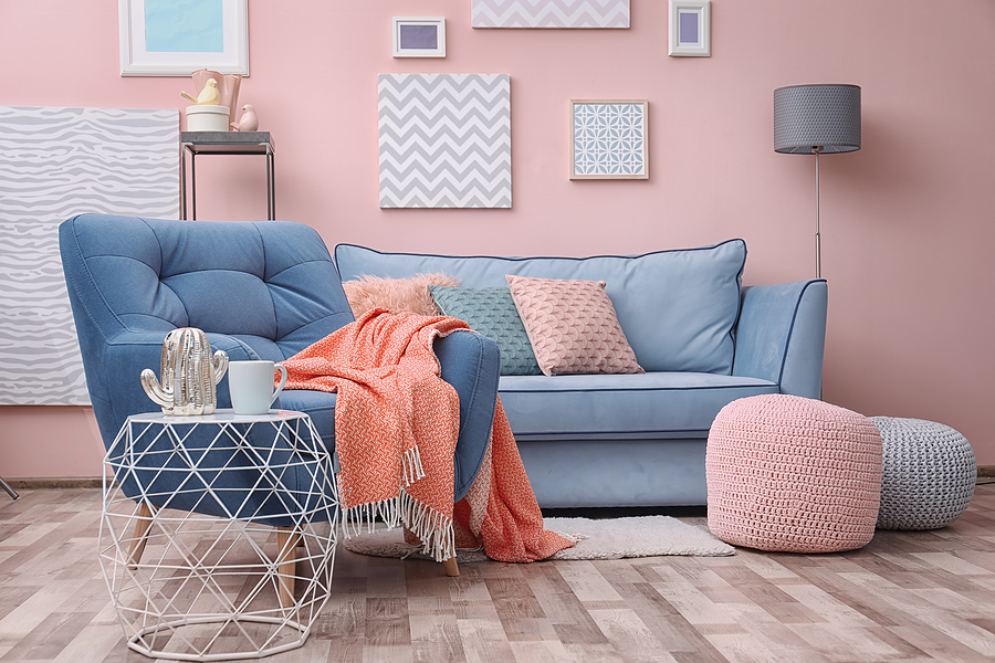 Modern living room interior with blue armchair and textured pillows and footstools