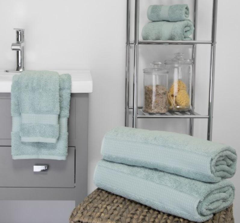 luxury sobel westex luxury hotel bath towels displayed over sink, bathrooom shelves and on top of wicker basket