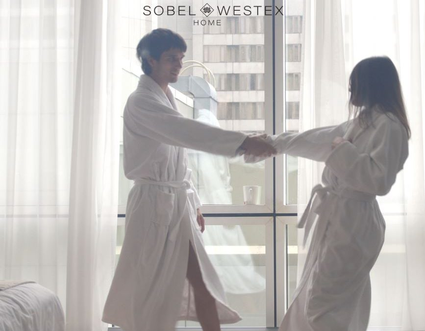 A couple dancing in a hotel room wearing luxury hotel spa bathrobes