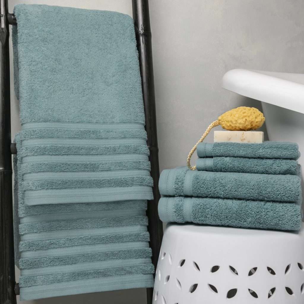 Sobel Westex luxury bath towel set iin smoke dust blue hanging on bamboo rack with spnge and soap for a luxury day spa experience