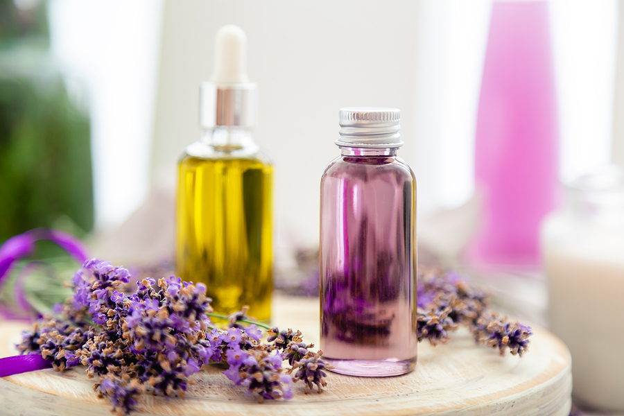 two aromatherapy bottles with lavender essential oils surrounded by fresh lavender flowers.