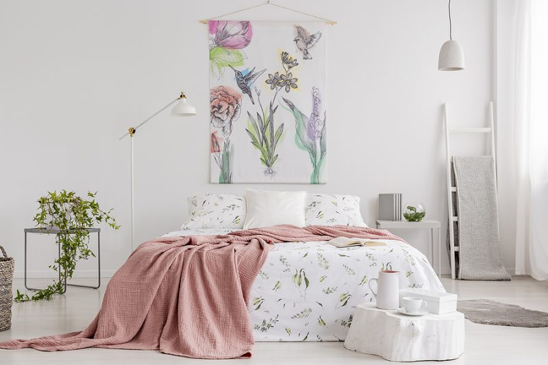 Spring colors pastel bedroom interior with a big bed in the middle and a painted fabric art on the wall.