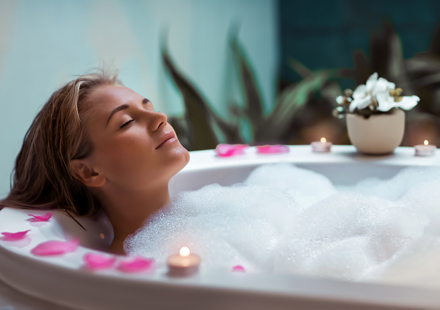 Portrait of a beautiful young woman taking bath with foam and flower petals by candlelight, enjoying dayspa in luxury spa hotel