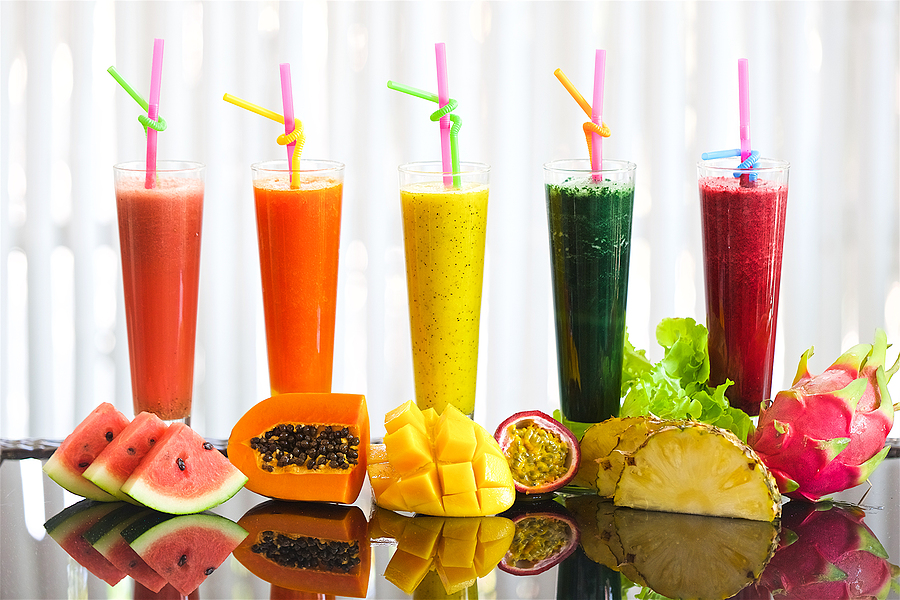 tropical fruit smoothie, on a table in glasses of watermelon neck with papaya pineapple mango and passion fruit and pithaya, salad greens drink, healthy drinks on a white background, mirror reflection of fruits and juices