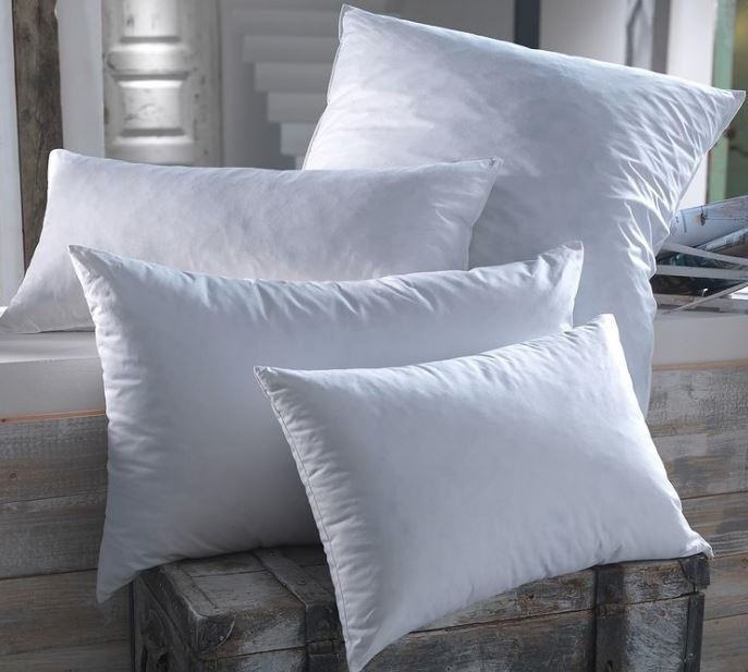 Four luxury hote; pillows of different sizes posed in a stylish pile