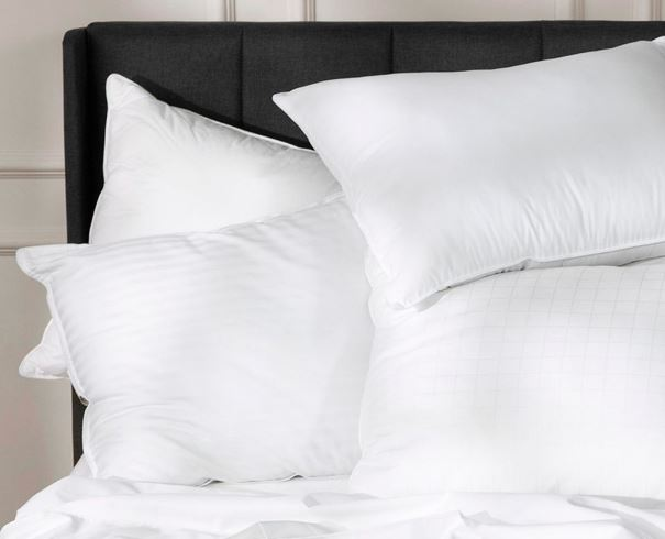 PIle of four Sobel Westex luxury hotel pillows on a hotel bed against the headboard