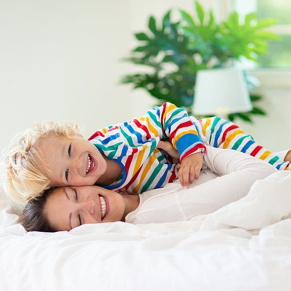 Mother and child playing in bed with clean white egyptian cotton sheets