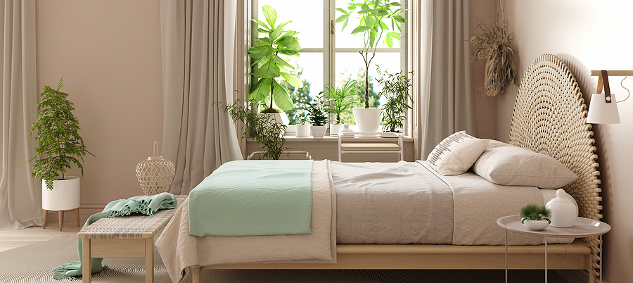 Bedroom interior with green plants and pastel colors mint green and beige bedding