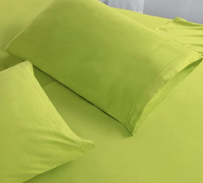 Spring green jersey cotton sheets on bed with two pillows