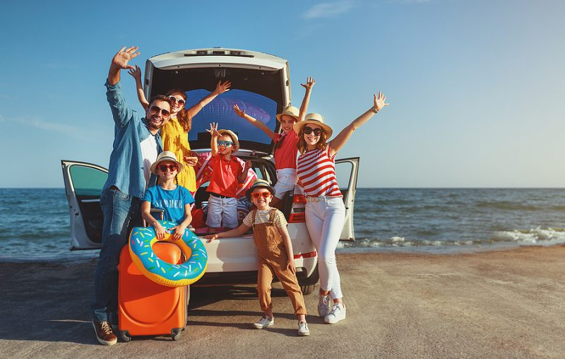 family at the beach waving from the back of their SUV with beach accessories