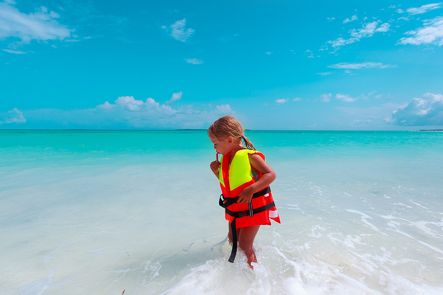 small girl wearing life jacket at the edge of the water at the beach demonstrating beach safety