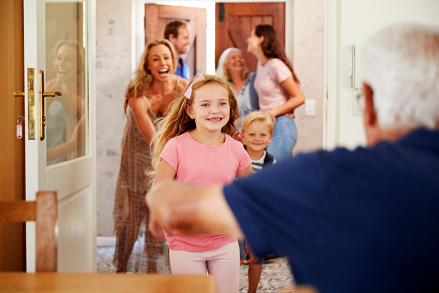 Happy grandparents greet arriving family with grandkids at family reunion for overnight visit as houseguests