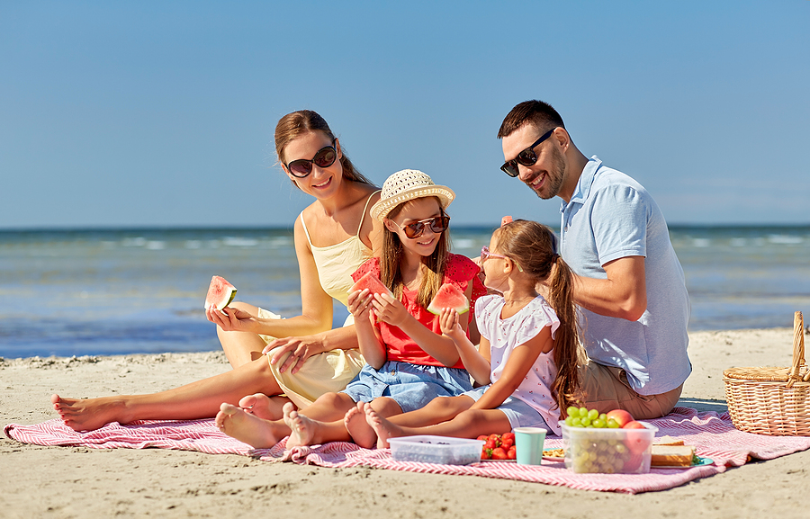 family of four on beach towel wiht picnic basket eating watermelon