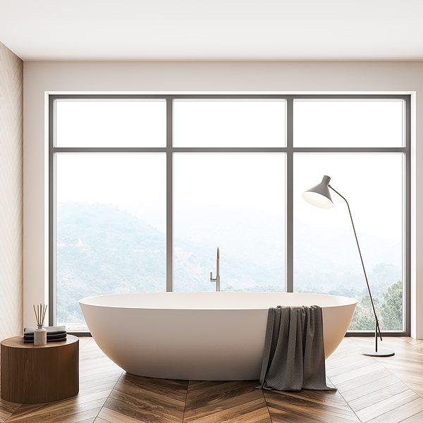 minimalist high end bathroom with white tub, gray bath towel, large windows and foggy mountain view