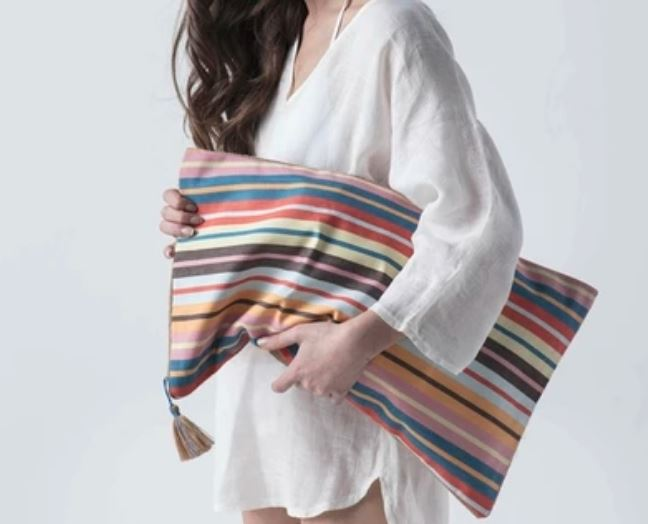 Girl in casual cotton shirt holding eco friendly pillow size cotton striped beach bag